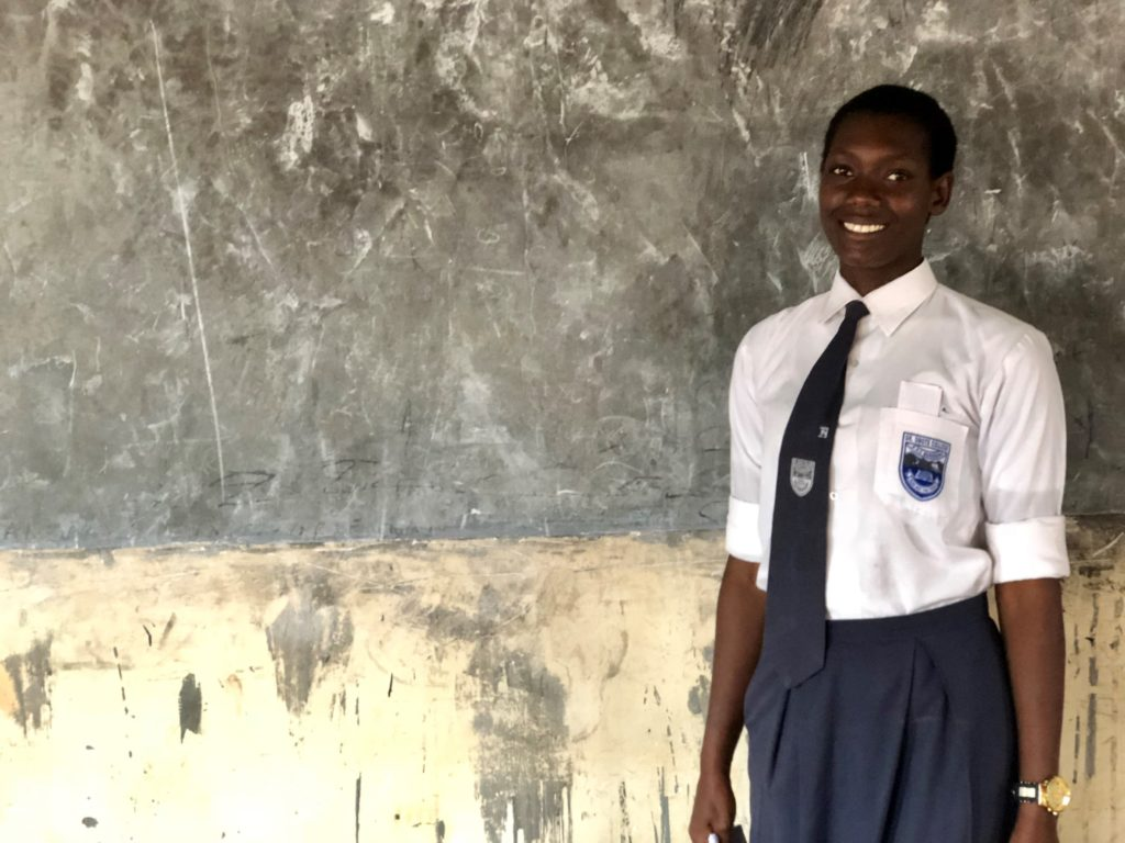 Pricilia stands in front of the white board in the girls' study room, which she advocated for. Girls education and empowerment concept