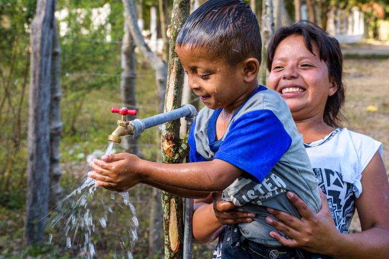 Johanna Hernandez, 23, holds her son David, 5, so he can wash his face and drink clean water flowing from one of the taps built by the community with funding from World Vision US. Photo credit: ©2019 World Vision, Jon Warren