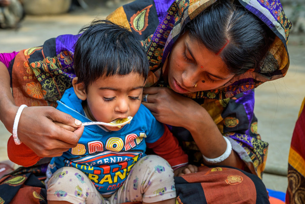A mother feeds her child at a courtyard feeding session, led by a nutrition facilitator from World Vision's Nobo Jatra program in southwest Bangladesh. The program, which is funded by U.S. foreign assistance, hopes to end the high rate malnutrition for women and children in the area. ©World Vision 2019, Jon Warren.