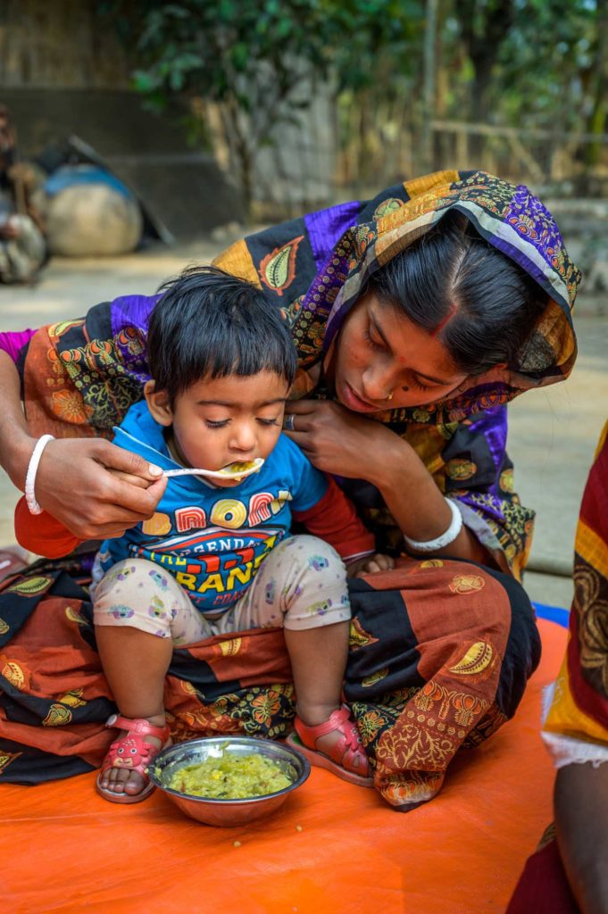 Mother feeds her child nutritious meal in Bangladesh.