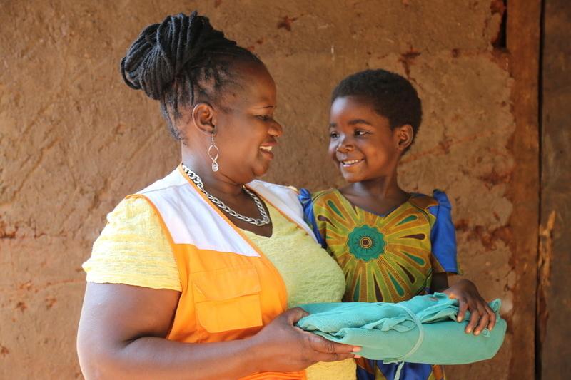 Chimwemwe Mizaya, a World Vision sponsorship coordinator, handing a mosquito net to Thandizo for her family.