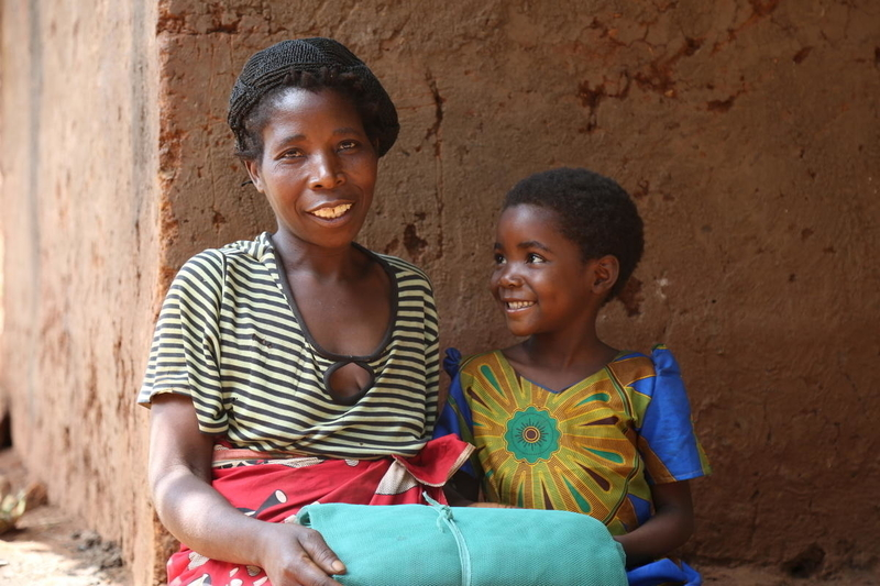 Thandizo and her mother receive mosquito nets to protect them from malaria.