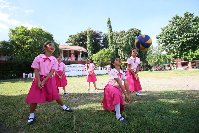 Girls play volleyball at a school in the Philippines.