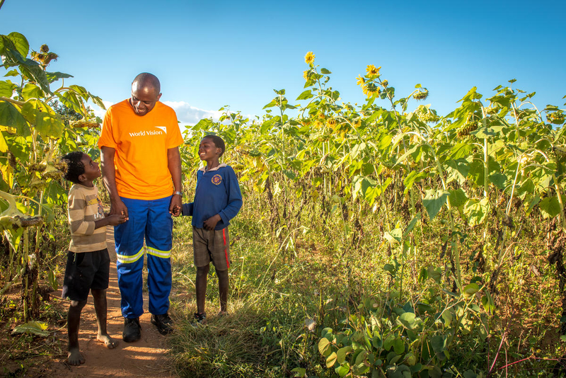 World Vision staff member and kids in cornfield