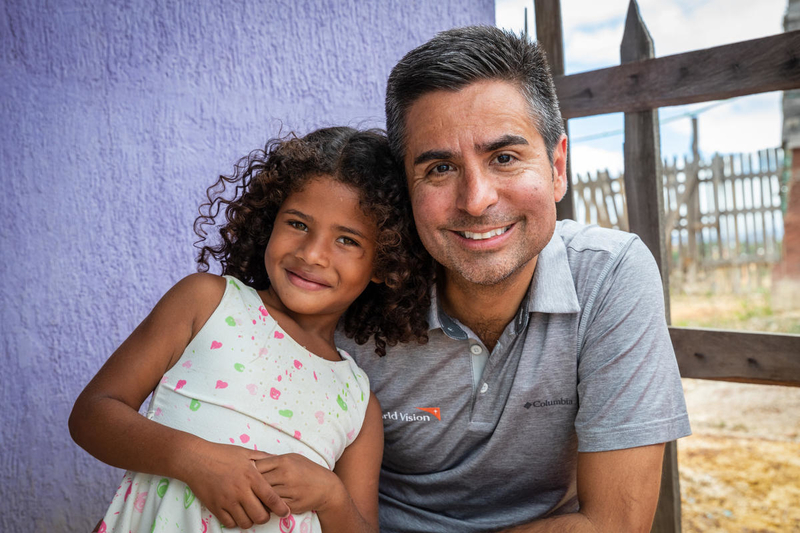 Migrant girl with World Vision president