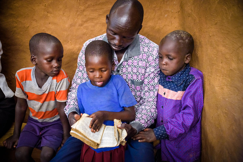 Man reading with kids in Kenya