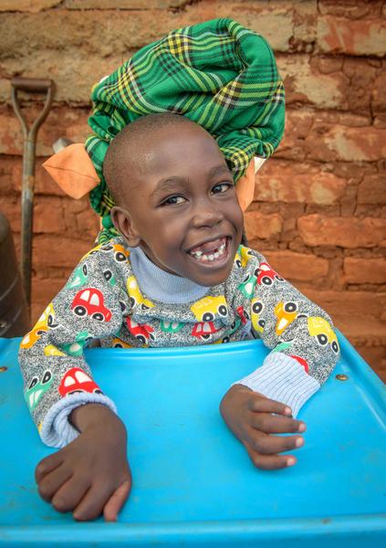 little boy smiles in wheelchair