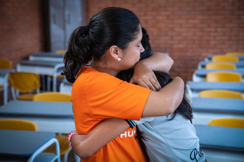 Staff hugs a young girl in Colombia