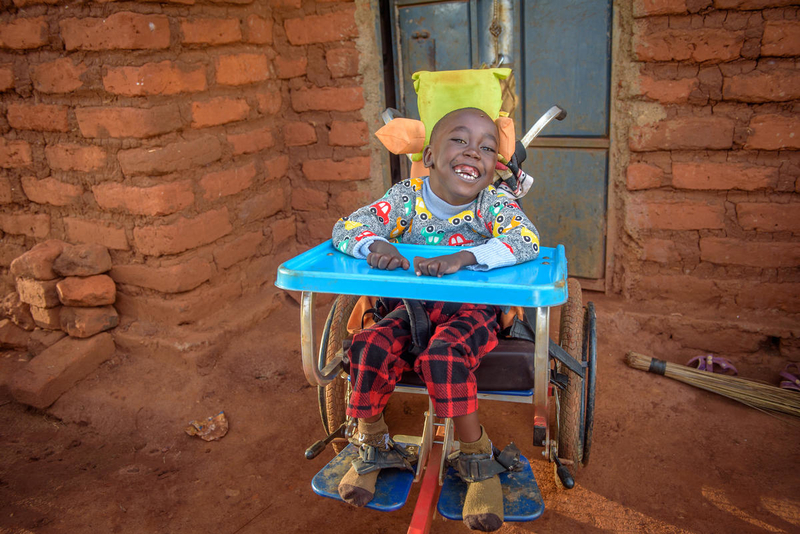 Dennis in his wheelchair from World Vision and USAID.