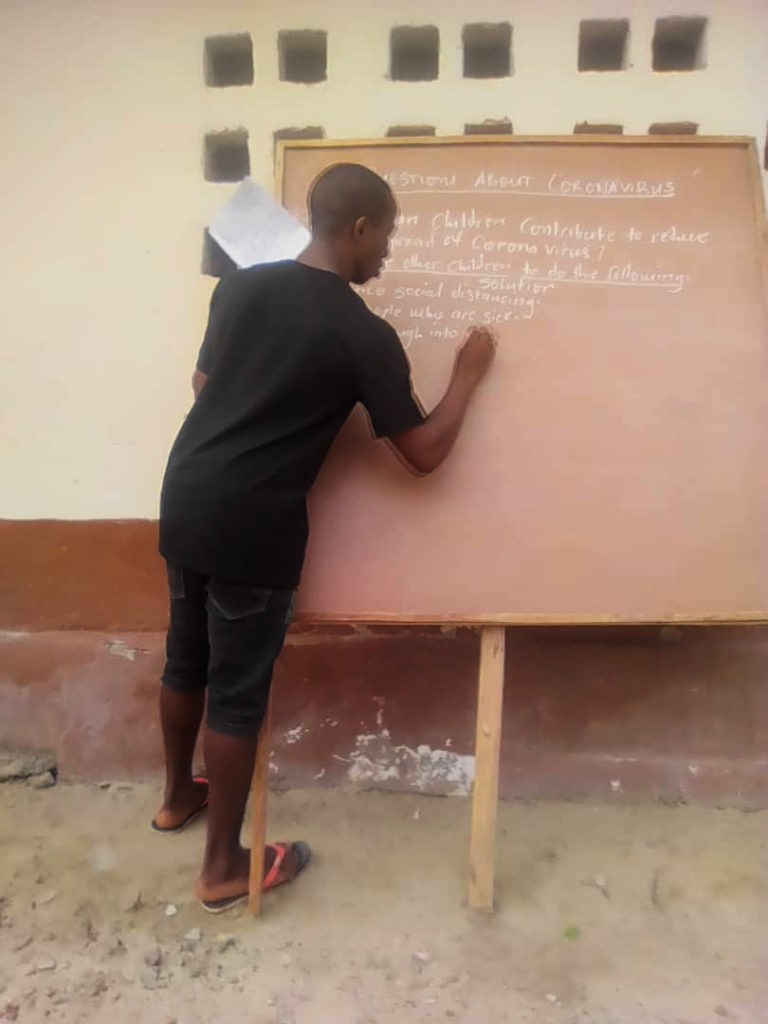 Teen writing on chalkboard about COVID-19