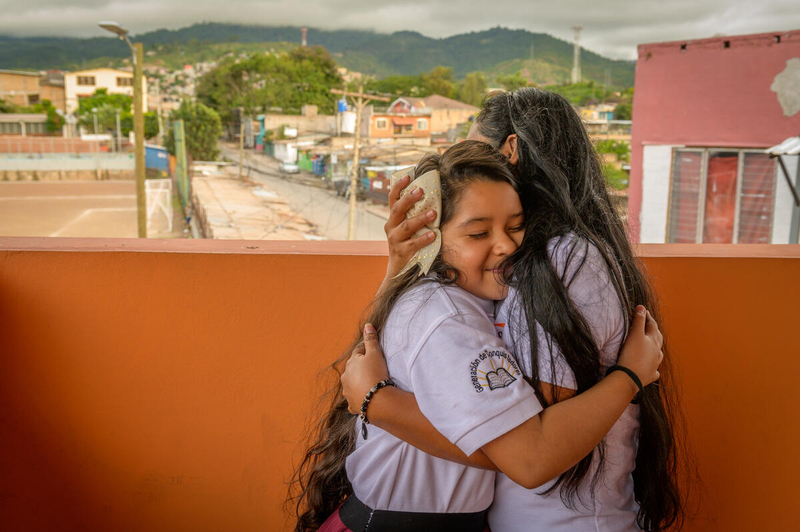 Young girl gets a hug at a church in Honduras