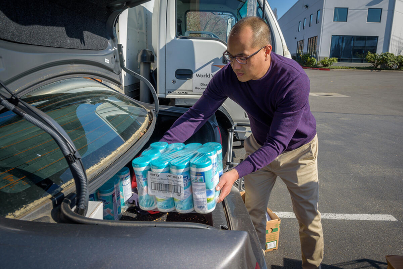 Dave loads sanitation supplies into his trunk.