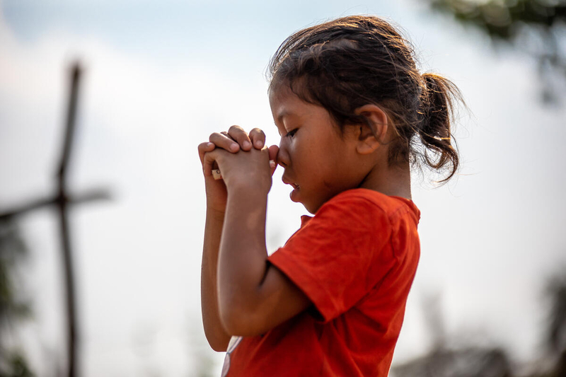Girl praying in Cambodia