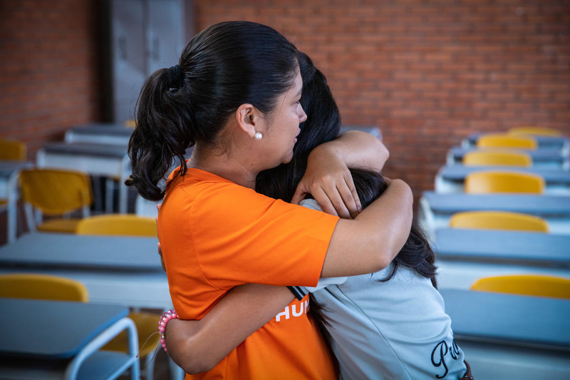 World Vision staff hugs girl in Colombia