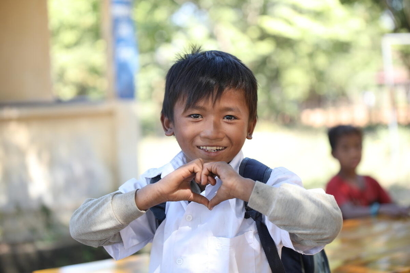 Little boy makes shape of heart with his hands