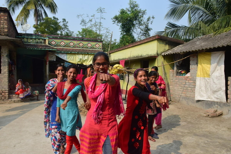 Women and girls in Bangladesh pose to show power against violence