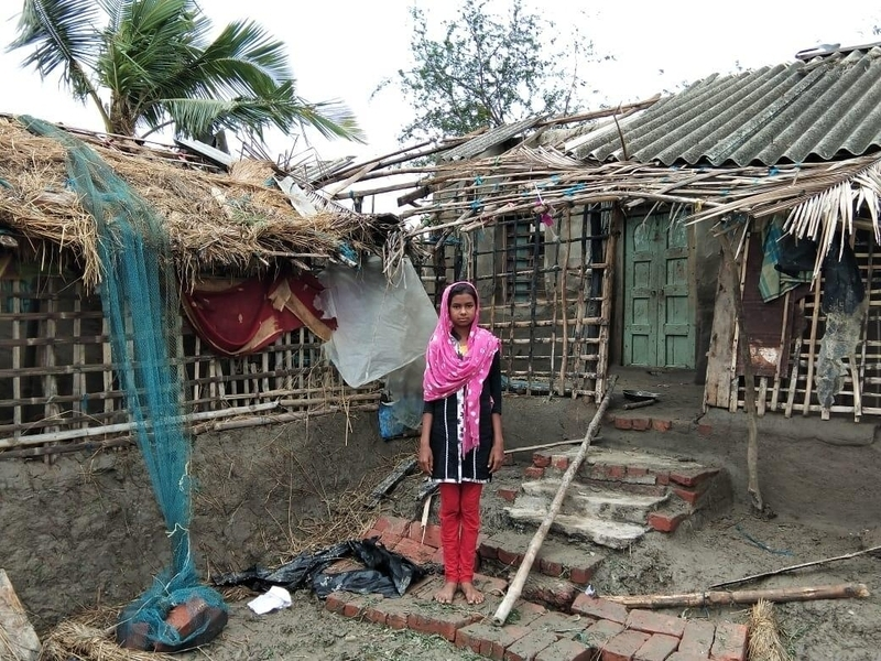 Girl in India stands outside home damaged by cyclone