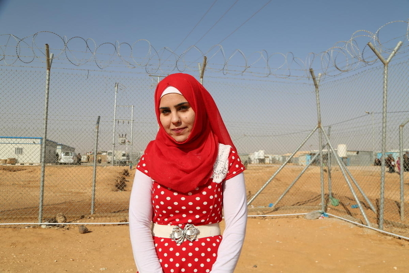 Young female refugee from Syria in front of a barbed wire fence