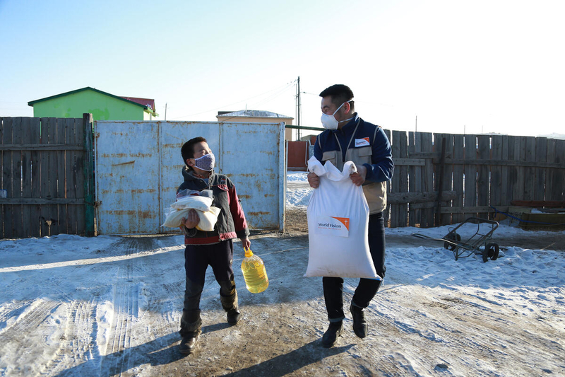 Young boy and World Vision staff carry food supplies