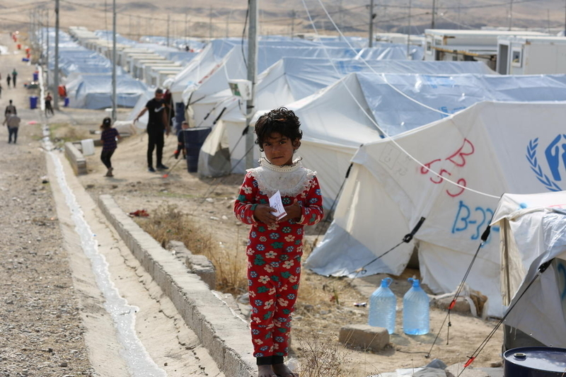 Young girl with refugee tents as background
