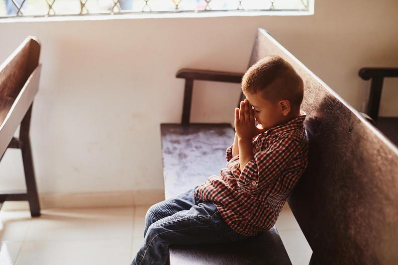 Young boy prays on empty church pew