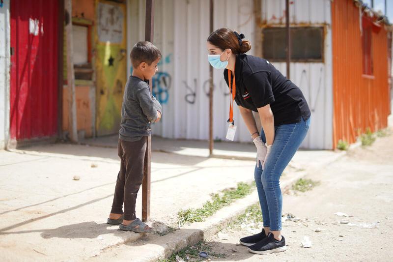 World Vision staff talks to Syrian boy