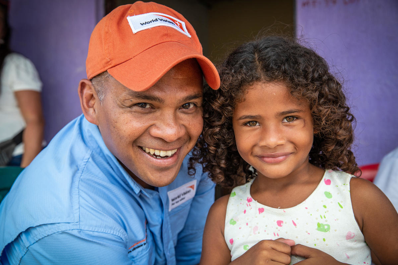 World Vision staff with young girl in Colombia