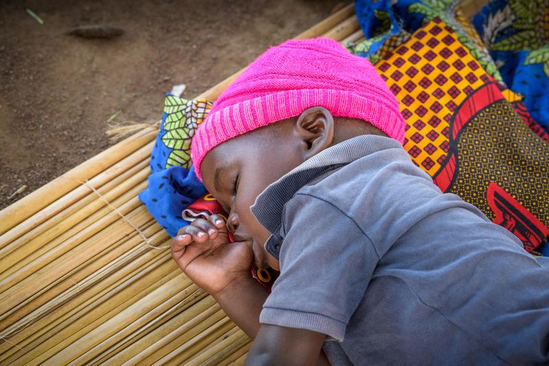 Sleeping toddler sucks his thumb in Uganda.