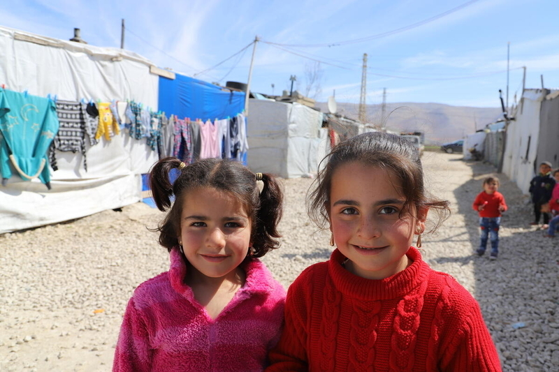 Two young Syrian refugee girls smiling