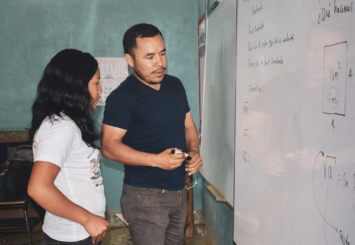 Digna and her teacher Fredy work on a math problem on the whiteboard during class. World Vision staff and U.S. government aid allowed Digna to avoid child labor in Honduras, and instead continue her education and dream of becoming a teacher in the future!